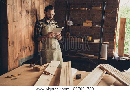 Workbench equipment vintage craftsmanship repair renovation remodel restoration profession concept. Smart thoughtful guy holding using pda pad for carving flooring engineering poster