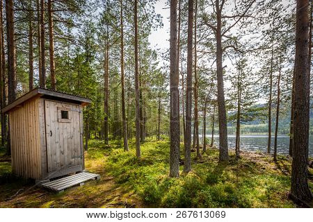 Outdoor Wooden Toilet In A Beautiful Sunny Forest Wilderness Landscape By A Lake.