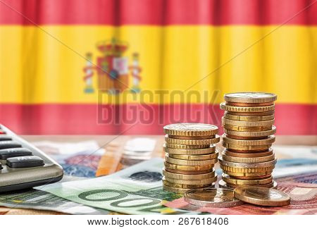 Euro Banknotes And Coins In Front Of The National Flag Of Spain