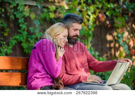 Couple With Laptop Sit Bench In Park Nature Background. Surfing Internet Together. Family Surfing In