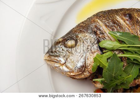 Dorada Fish Head Close Up. Grilled Dorade On A White Plate With Sauce, Arugula On A White Plate Isol