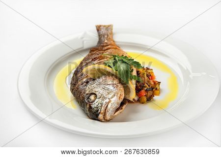 Grilled Dorade On A White Plate With Sauce, Arugula On A White Plate Isolated On White Background