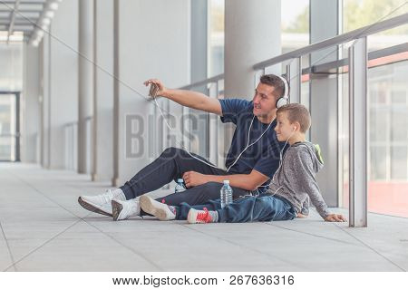 Little Boy And His Father Doing Stretching Legs Exercises  Together At A Sports Center. Father And S