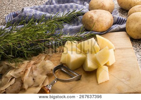 Peel And Cut Raw Organic Potato With Rosemary On A Wooden Board