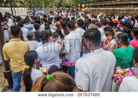 Kandy, Sri Lanka - July 19, 2016: White Clothed Buddhist Devotees Wait In A Queue At The Entrance To