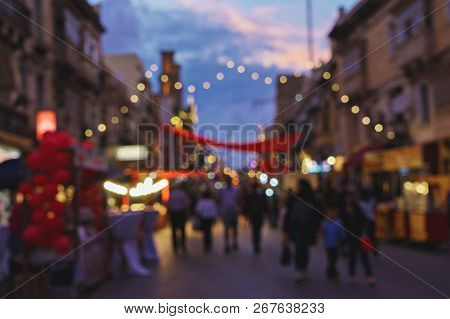 Blurred Background Of Christmas Fair On Old Town Street. Traditional Christmas Market Time Concept W