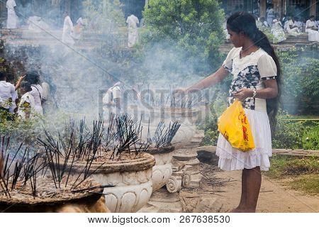 Kandy, Sri Lanka - July 19, 2016: White Clothed Buddhist Devotee Lights Incense Sticks At The Temple