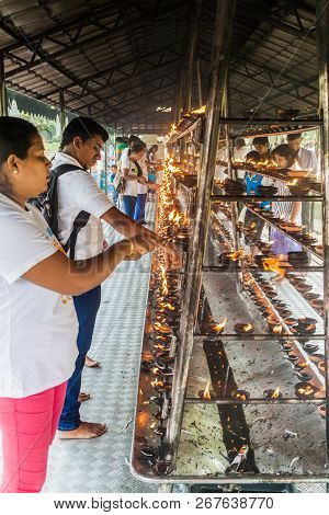Kandy, Sri Lanka - July 19, 2016: White Clothed Buddhist Devotees Light Candles At The Temple Of Sac