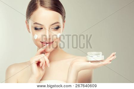 Beautiful Young Woman With Clean Fresh Skin. Girl Holding Cream In Her Hand .spa And Face Care