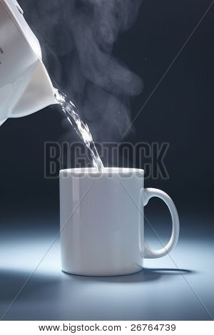 stock image of pouring hot drink to the mug