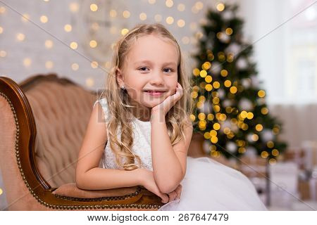 Portrait Of Cute Little Girl In Decorated Living Room With Christmas Tree