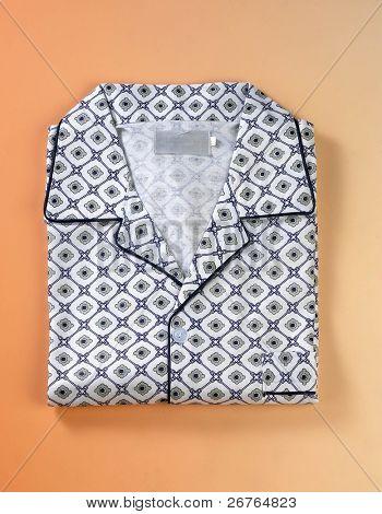 Folded pyjamas top on orange background.