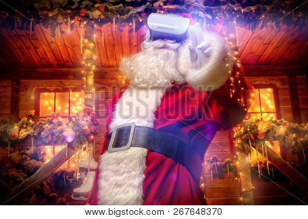 Cool modern Santa Claus in virtual reality glasses standing near his decorated house. Computer games. Christmas and New Year concept.