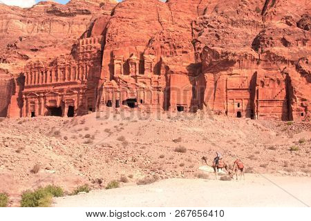 Bedouin riding a camel on Street of facades in Petra (Red Rose City), Jordan. UNESCO world heritage site