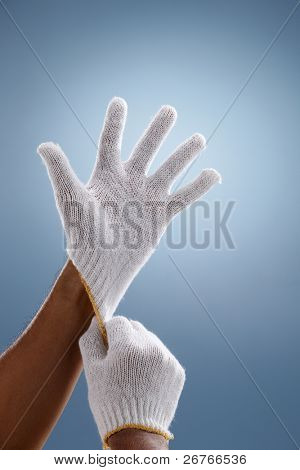 Hands putting on gloves over a creative blue background.