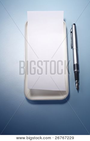 blank Reciept on tray with a pen isolated on blue background. poster