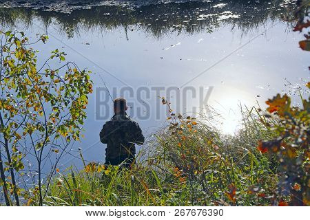 Fisherman Standing On Riverside And Trying To Catch Fish. Male Hobby. Recreation