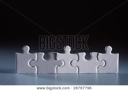 poster of Five puzzle pieces arranged together.