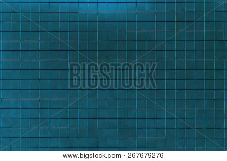 Close-up Of A Dark Blue Colored Tiled Wall. View To A Blue Shiny Metallic Wall. Geometric Shapes And