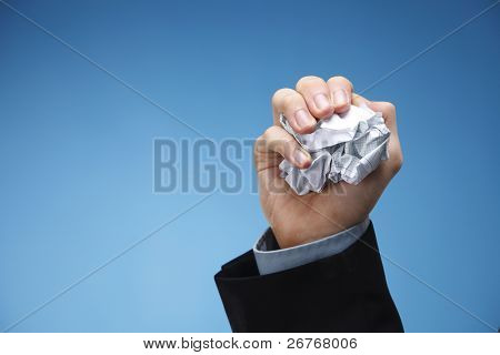 Human hand holding a scrunched up paper.