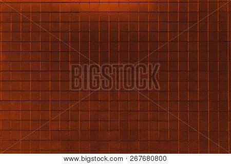 Close-up Of A Brown Colored Tiled Wall. View To A Metallic Copper Wall. Geometric Shapes And Backgro