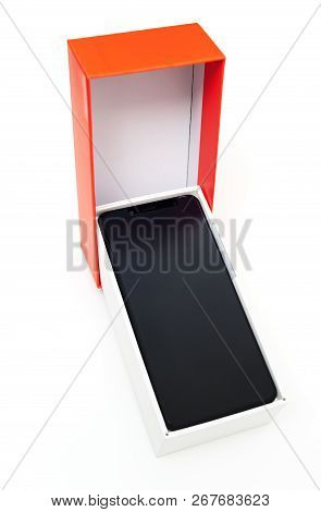 The Black Smartphone Is In The White Box. Near Is The Orange Top.