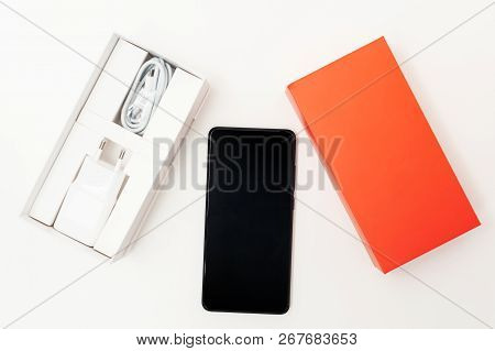 Black Smartphone On A White Background. Along With This There Is A Box With A Power Supply And A Cha