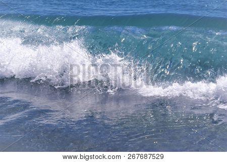 A Refreshing Background Image Of A Wave Crashing Onto Shore.