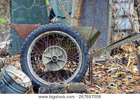 Old Rusty Wheelbarrow With A Big Wheel In The Yard