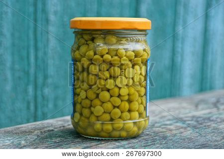 Green Canned Peas In A Closed Glass Jar On A Gray Table