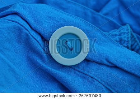 Big Blue White Plastic Button On Crumpled Clothes