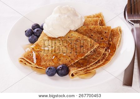 Delicious Pancakes Or Crepes With Blueberries, Maple Syrup And A Dollop Of Whipped Cream.