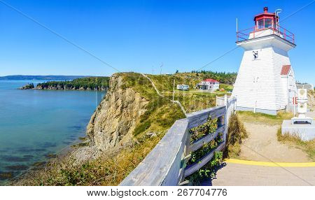 View of the Cape Enrage lighthouse, shoreline and cliffs, in New Brunswick, Canada poster