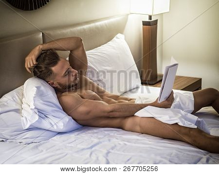 Young Man Lying In Bed Reading A Book