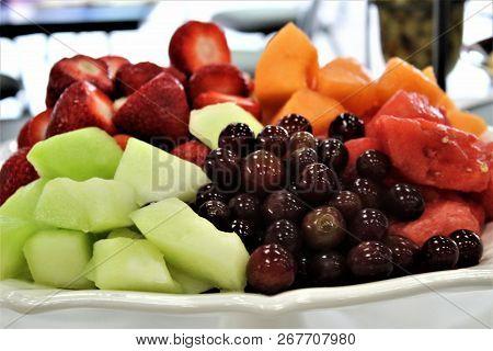 Closeup Shot Of Fresh Fruit Piled On A White Platter.