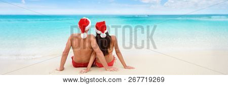 Christmas tropical sun vacation destination vacation holidays santa hat couple relaxing sitting on beach banner background for text advertisement for New Year holiday season. Blue ocean copy space.