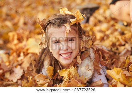 Child girl is lying and playing in fallen leaves in autumn city park.