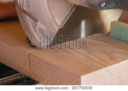 Worker sawing a wood board with a circular saw. Close-up hands. poster