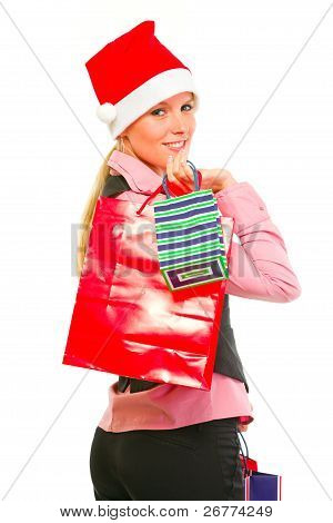 Smiling Female Business Clerk In Santa Hat With Shopping Bags