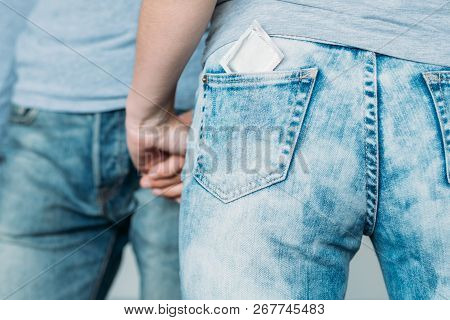 Safe Love And Health Concept. Condom Protection From Hiv And Aids. Backview Of A Woman With A Contra