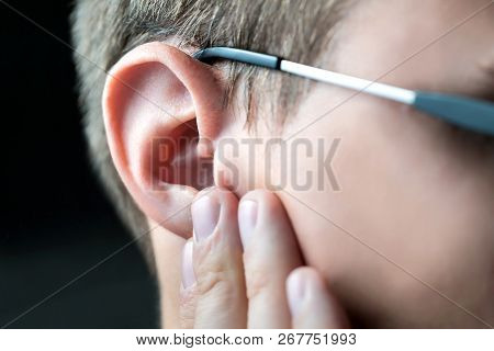 Man Holding Hurting Ear With Hand. Earache And Pain. Otitis Or Infection In Ear Canal. Impaired Hear