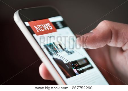 Mobile News Application In Smartphone. Man Reading Online News On Website With Cellphone. Person Bro