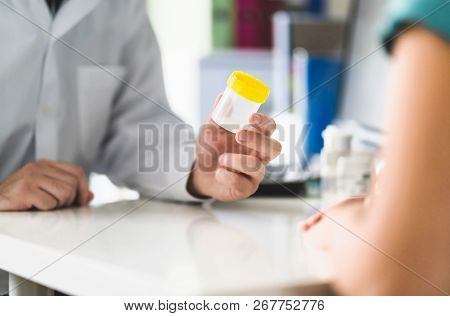 Doctor, Patient And Urine Test Cup. Physician Giving Pee Container To A Woman In Clinic Or Hospital