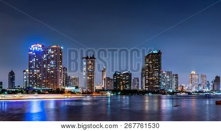 Cityscape Of Modern Building Near The River In The Night. Modern Architecture Office Building. Skysc