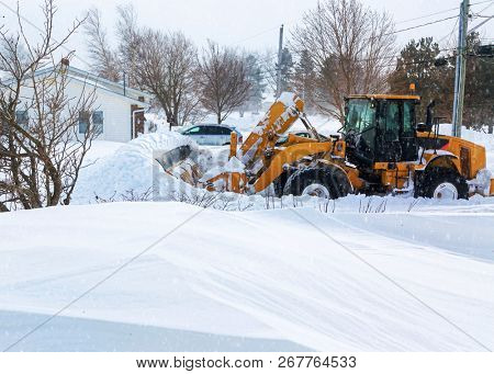 Large snowplow pushes through a heavy snowfall on a suburban street after a snow storm.