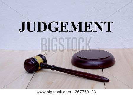 Judgement Written On The Wall With Gavel On Wooden Background. Law Concept.