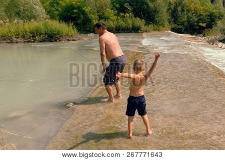 Dad And Son Bathe In The Mountain River In The Summer On A Clear Day.
