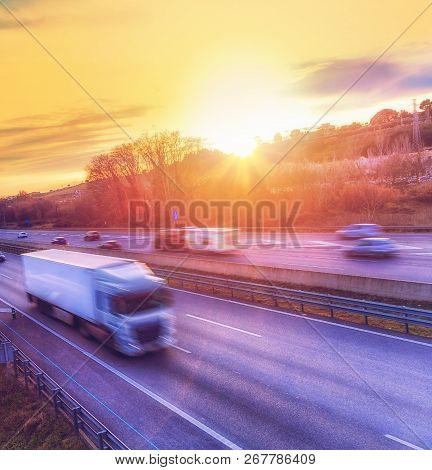 Heavy Truck Speeding On Highway At Sunset. Motion Blur.