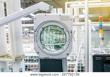 Large Magnifying Glass On A Hanging Mount On A Production Machine.