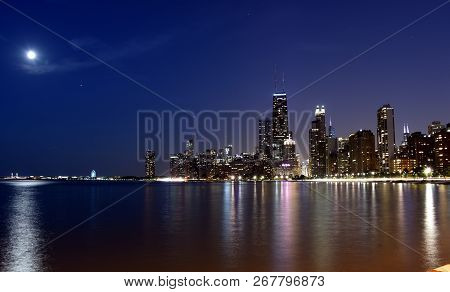 Chicago City Urban Skyscraper With John Hancock Center And A Full Moon Over Navy Pier At Night At Do